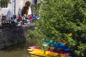 gente en terrazas al lado del rio